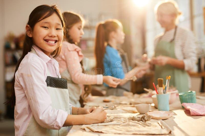 Lächelndes asiatisches Mädchen im Tonwaren-Studio stockbilder