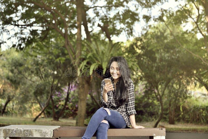 Lächelndes asiatisches Mädchen mit Handysitzen stockfotos