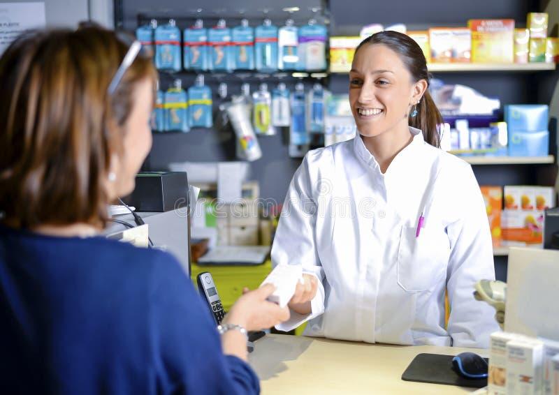 Lächelndes attraktiver junger Rothaarigeapotheker überreichendes prescri stockbild