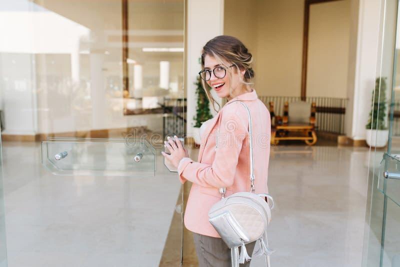Lächelndes attraktives Mädchen, das große Glastür in Büro, Hotel, Geschäftszentrum betritt Tragende stilvolle Gläser, graue Hosen lizenzfreies stockfoto