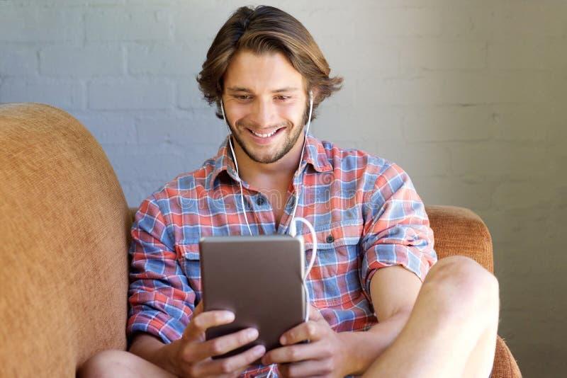 Lächelndes aufpassendes Video des jungen Mannes auf Tablette mit Kopfhörern lizenzfreies stockfoto