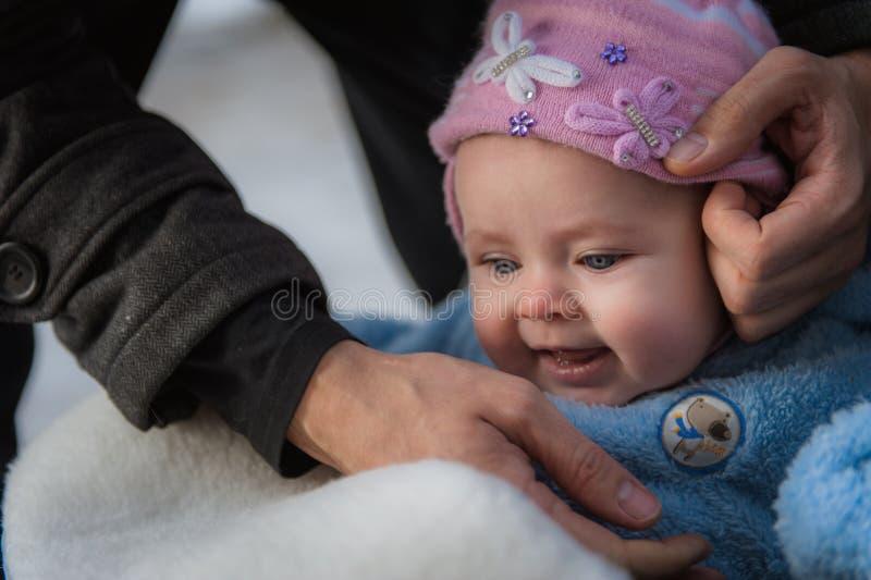 Lächelndes Baby, das im Schlitten sitzt Glückliches Säuglingsmädchen stockfotos