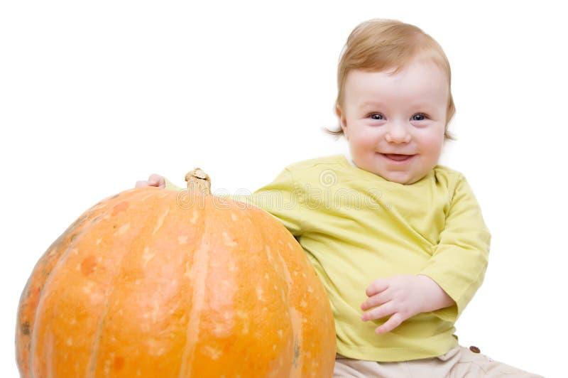 Lächelndes Baby, das mit Kürbis spielt stockfotos