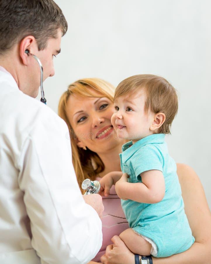 Lächelndes Baby, das von einem Doktor verwendet ein Stethoskop überprüft wird lizenzfreie stockfotos