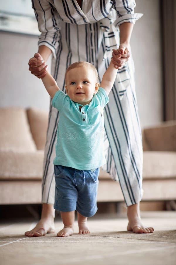 Lächelndes Baby, das zuerst Schritte mit Mutter macht stockbilder