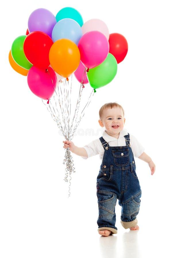 Lächelndes Baby mit Bündel bunten Ballonen lizenzfreies stockbild