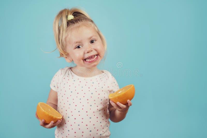 Lächelndes Baby mit einer Orange stockfotos