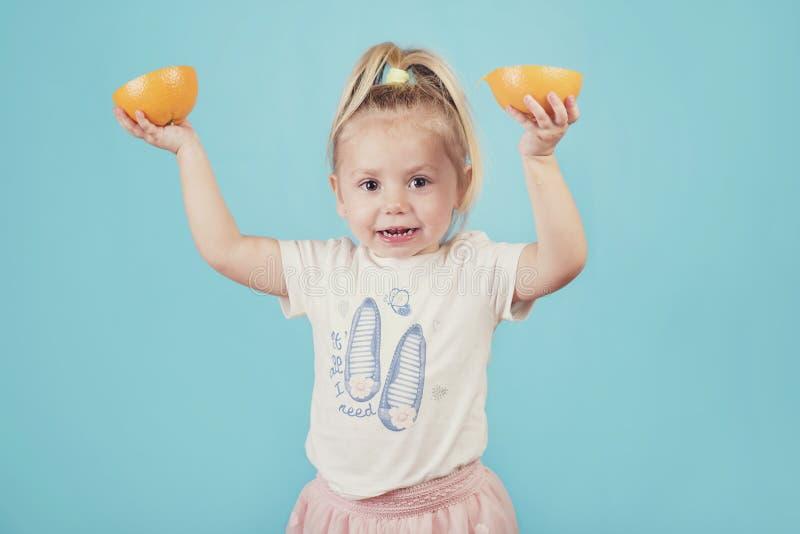Lächelndes Baby mit einer Orange lizenzfreies stockbild