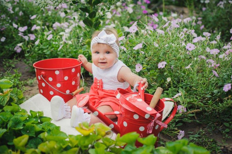 Lächelndes Baby sitzt auf dem grünen Gras und den Blumen mit dott stockfotos