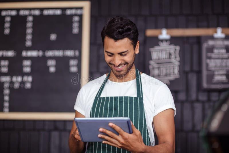 Lächelndes barista unter Verwendung der Tablette lizenzfreie stockfotografie