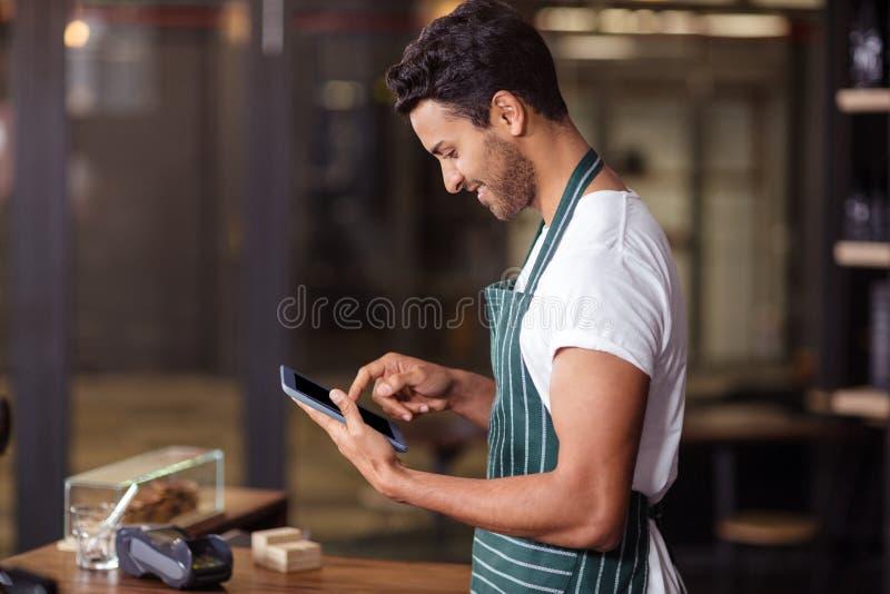 Lächelndes barista unter Verwendung der Tablette stockfoto