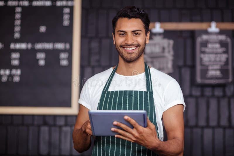 Lächelndes barista unter Verwendung der Tablette und Betrachten der Kamera stockbild