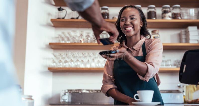 Lächelndes barista unter Verwendung nfc Technologie für Zahlung von einem Kunden lizenzfreie stockfotos