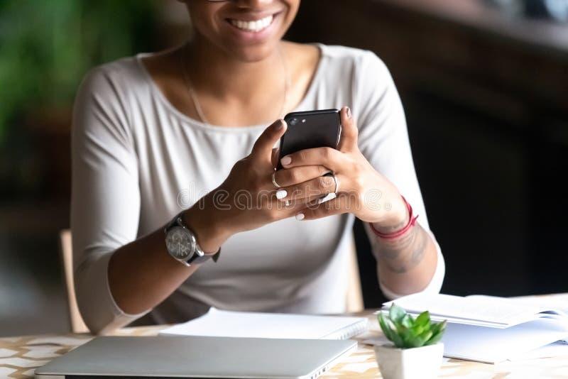 Lächelndes biracial Frauengriffmobiltelefon, das online plaudert lizenzfreies stockbild