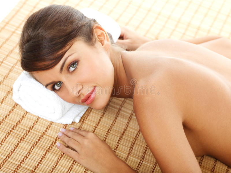 Lächelndes bloßes Frauen-Lügen anfällig am Badekurort stockfotos