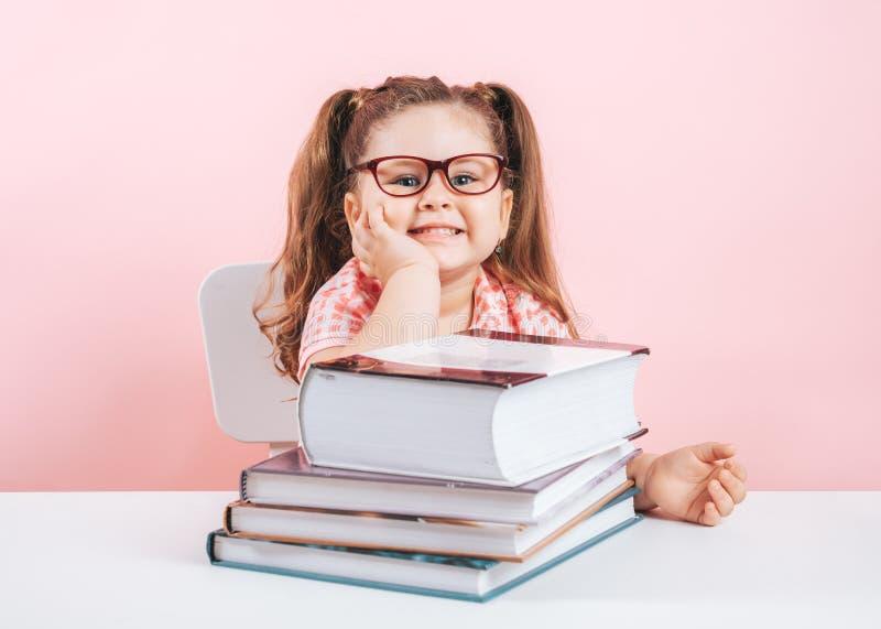 lächelndes blondes kleines nettes Mädchen, das auf Büchern studiert stockfotos