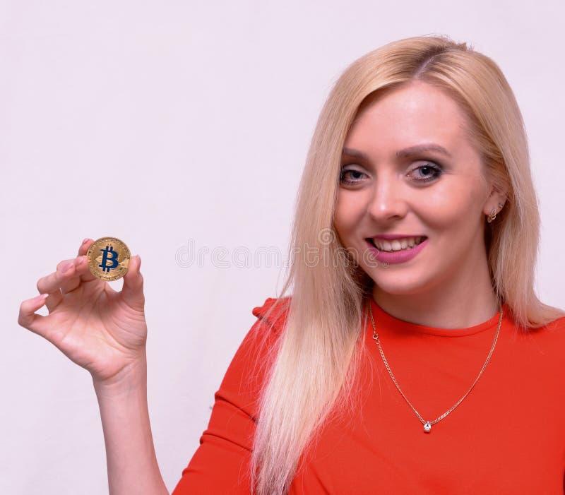 Lächelndes blondes Mädchen im roten Kleid halten goldenes bitcoin in zwei Fingern lizenzfreie stockbilder