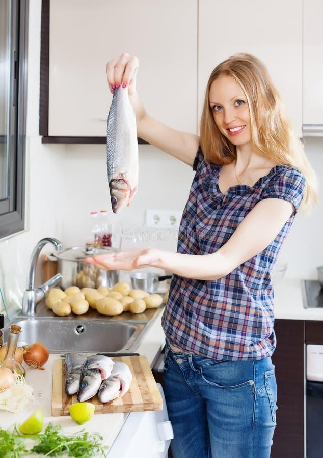Lächelndes blondes Mädchen mit rohen Fischen lizenzfreie stockbilder
