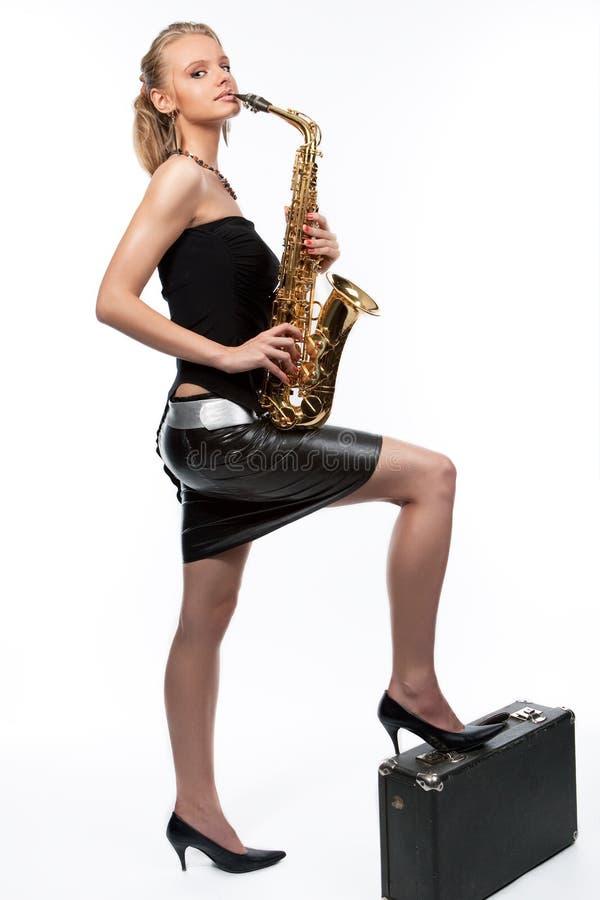 Lächelndes blondes Mädchen mit Saxophon und Koffer stockfotografie