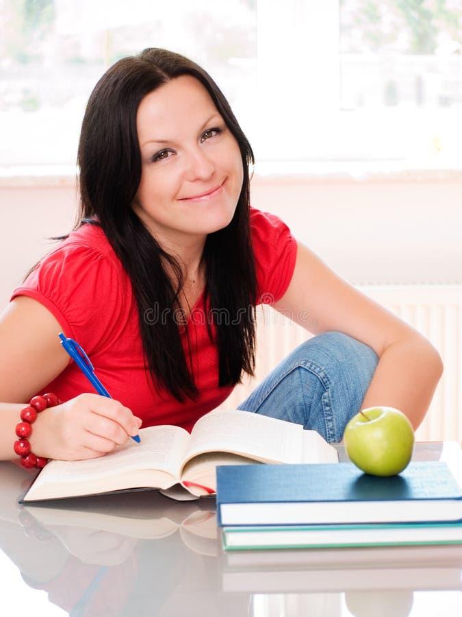 Lächelndes Brunettefrauenstudieren lizenzfreie stockbilder