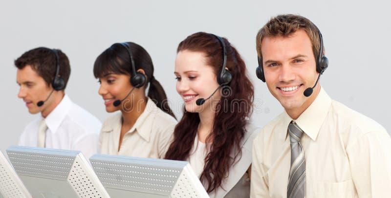 Lächelndes businessteam, das in einem Kundenkontaktcenter arbeitet lizenzfreie stockfotografie
