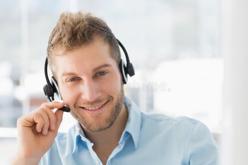 Lächelndes Call-Center-Vertreter, das einen Kopfhörer trägt stockfotografie