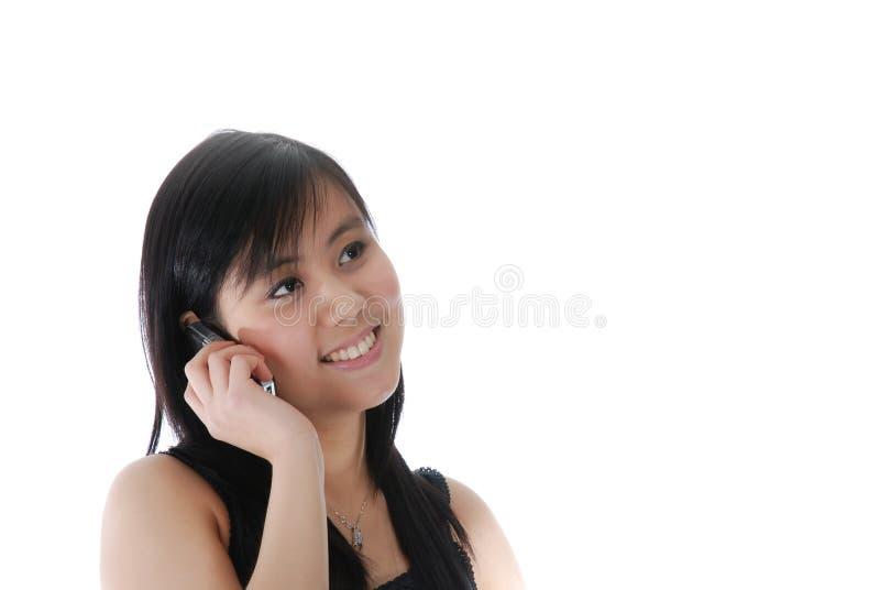 Lächelndes chinesisches Mädchen, das über dem Telefon spricht stockfoto