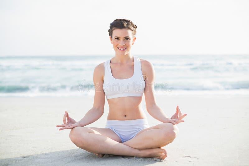 Lächelndes dünnes braunes behaartes Modell in der weißen Sportkleidung, die in Lotussitz meditiert stockfoto