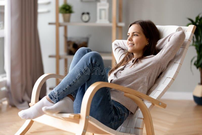 Lächelndes Entspannungszurück zu Hause sich lehnen der jungen Frau im bequemen Stuhl lizenzfreie stockbilder