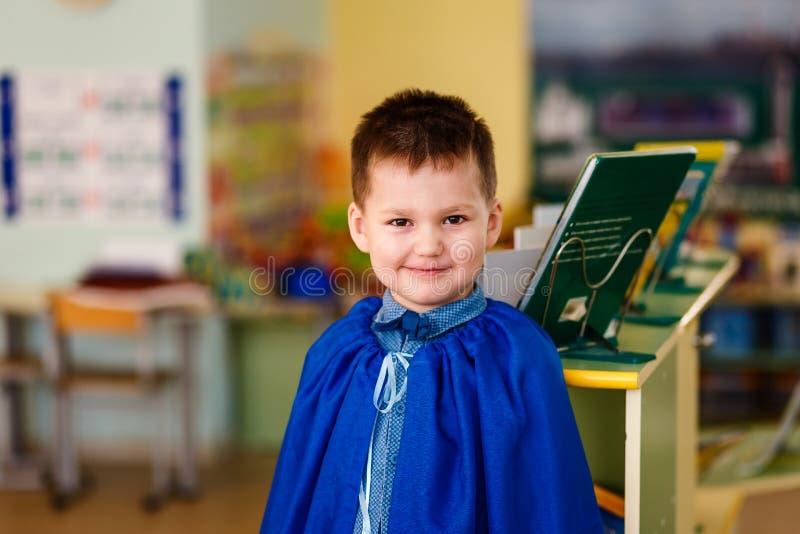 Lächelndes fünfjähriges Kind auf einem unscharfen Kindergartenhintergrund lizenzfreie stockfotografie