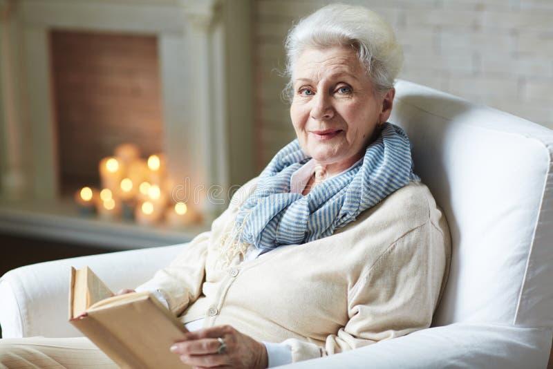 Lächelndes Frauenlesebuch im Ruhestand stockfotos