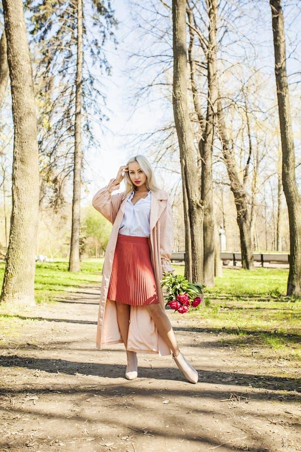 Lächelndes Frauenmode-modell mit Blumen draußen lizenzfreies stockfoto
