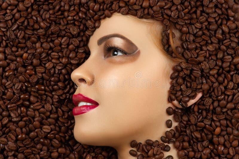 Lächelndes Frauenprofilgesicht in den Kaffeebohnen stockfotografie