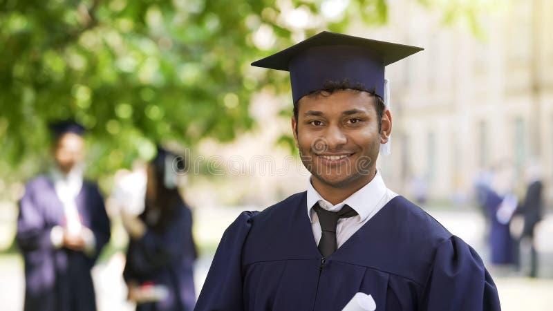 Lächelndes freuendes Diplom des hispanischen Studenten im Aufbaustudium, Erfolg, werfend für Kamera auf stockbild