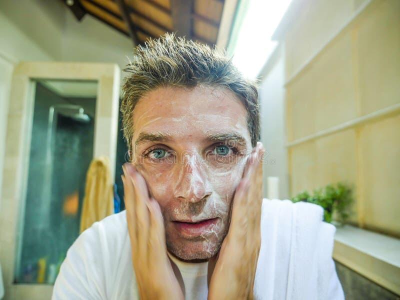 Lächelndes frisches zu Hause Badezimmer des glücklichen und attraktiven kaukasischen Mannes, das sein Gesicht mit der exfoliant S stockfoto