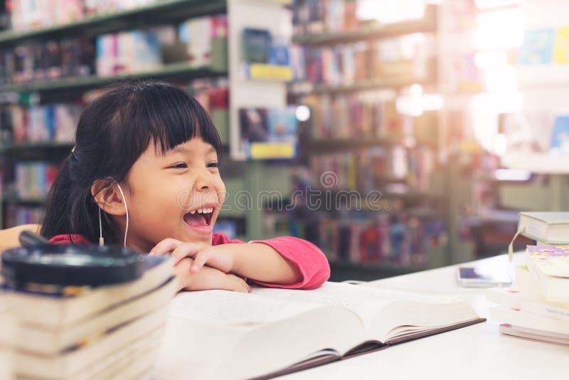 Lächelndes gelesenes Buch des Kindermädchenrosa-Stoffes an der Bibliothek stockbild