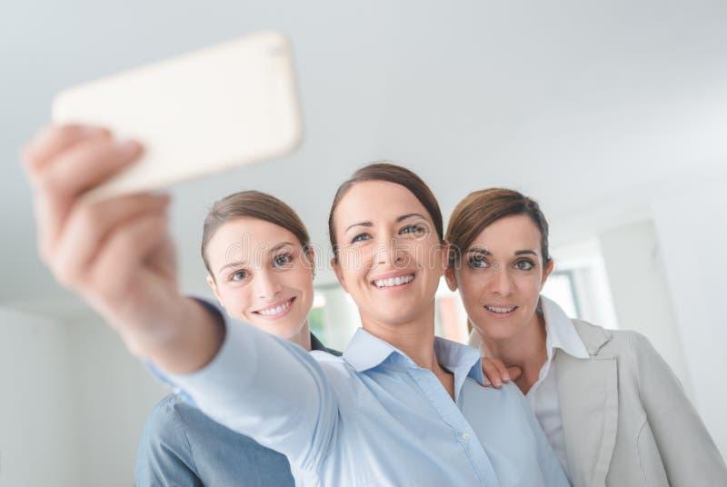Lächelndes Geschäftsfrauteam, das ein selfie nimmt stockfotos