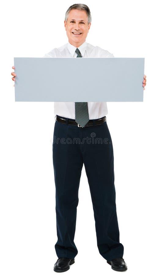Lächelndes Geschäftsmannholdingschild lizenzfreies stockfoto