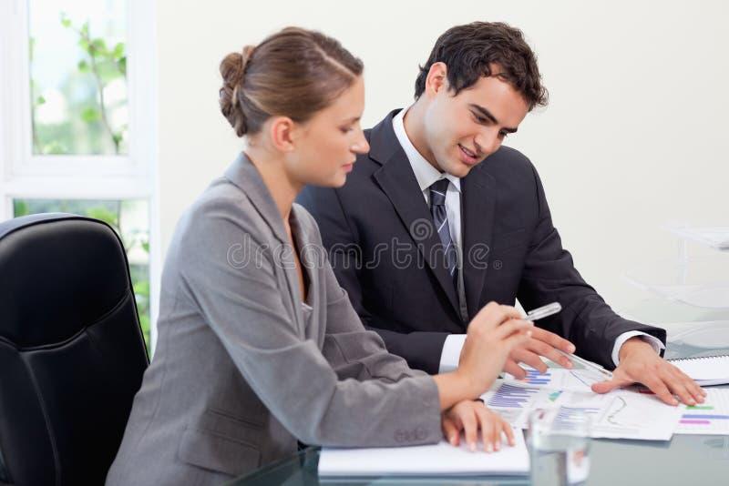 Lächelndes Geschäftsteam, das Statistiken studiert lizenzfreies stockfoto