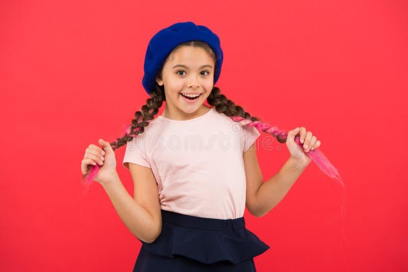 Lächelndes Gesicht des Kinderkleinen netten Mädchens, das im roten Hintergrund des Hutes aufwirft Wie man französisches Barett tr lizenzfreie stockbilder