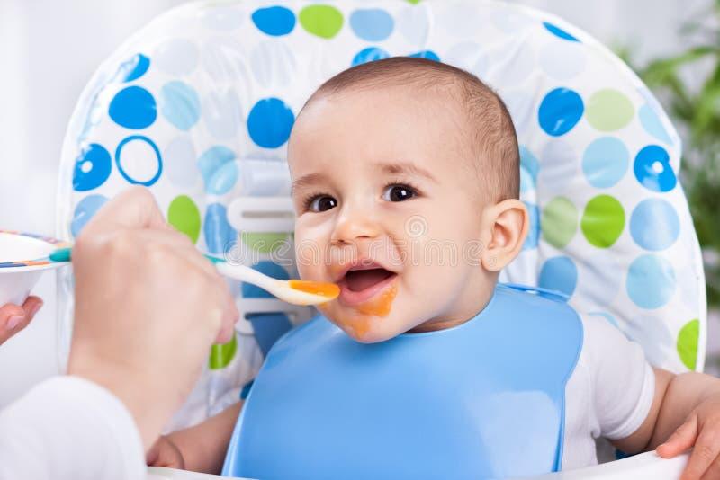 Lächelndes glückliches Baby, das mit Löffel isst lizenzfreies stockfoto