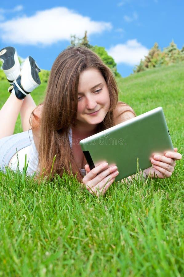 Lächelndes glückliches Mädchen, das auf Gras mit Tablette liegt. stockbild