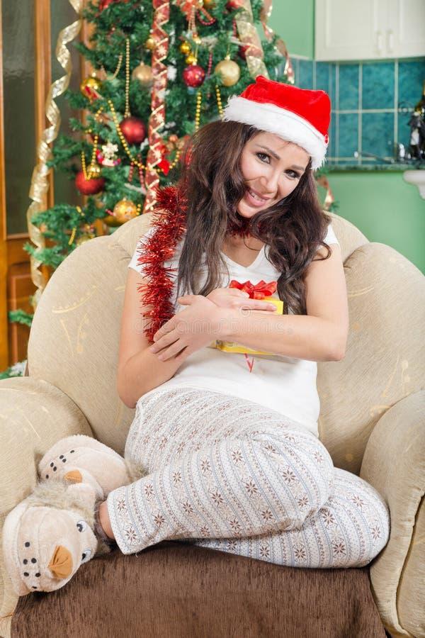 Lächelndes glückliches Mädchen, das den roten Hut hält Weihnachtsgeschenkbox trägt stockfoto