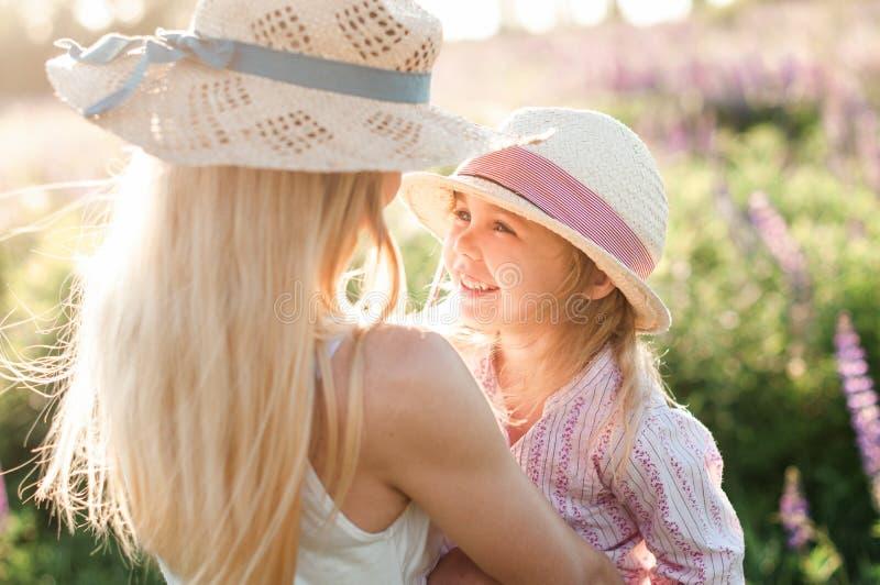 Lächelndes hübsches Mädchen an ihrer Mutter in ihren Armen lizenzfreie stockbilder