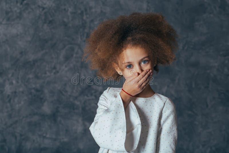 Lächelndes hübsches Mädchen mit Locken bedeckt ihren Mund mit ihrer Hand lizenzfreies stockfoto