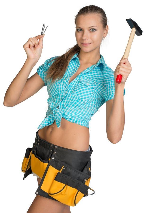 Lächelndes hübsches Mädchen mit Werkzeug schnallen das Halten des Hammers um lizenzfreie stockfotografie