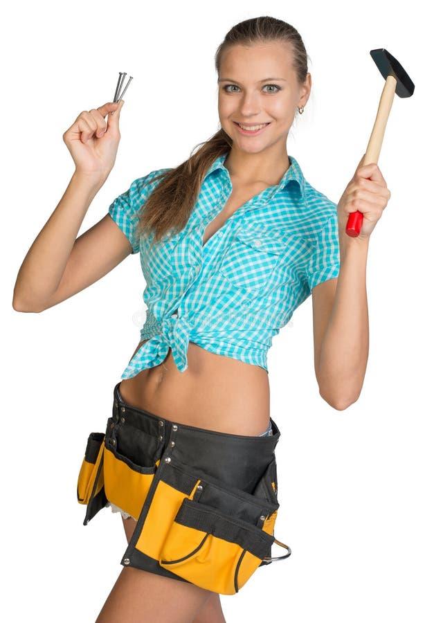 Lächelndes hübsches Mädchen mit Werkzeug schnallen das Halten des Hammers um lizenzfreie stockbilder
