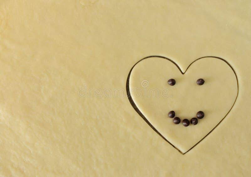 Lächelndes Herz mit Schokoladenaugen und das Lächeln, das vom Teig mit Kopie gemacht wird, sperrt Draufsicht Romantisches Konzept stockbilder