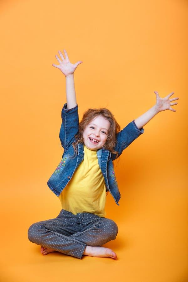 Lächelndes jähriges Mädchen sieben mit den Händen angehoben auf orange Hintergrund stockfotos
