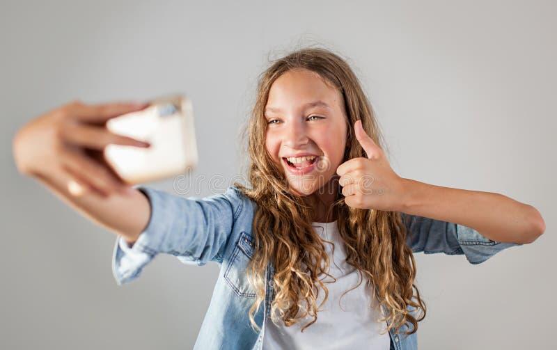 Lächelndes jugendlich Herstellungsselfie Foto auf Smartphone über nettem Mädchen des weißen Hintergrundes stockfotografie